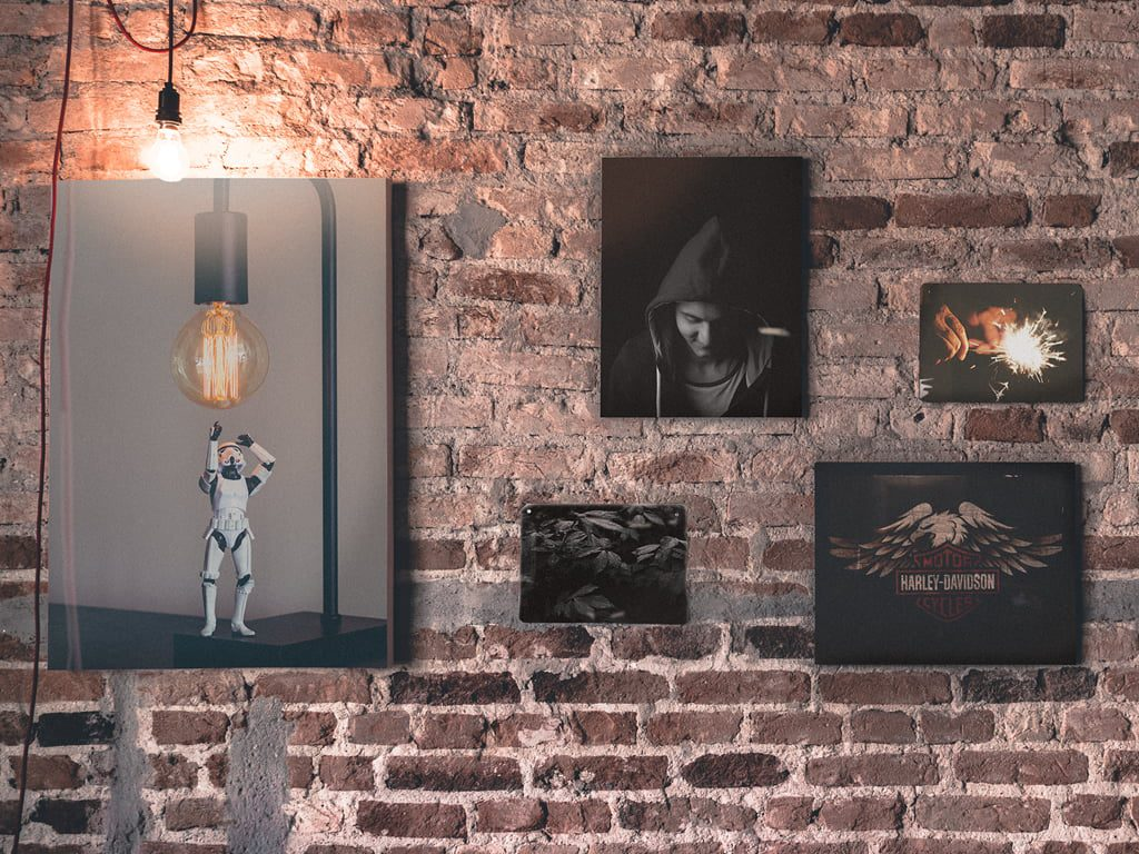Collection of wall art hung on brick wall