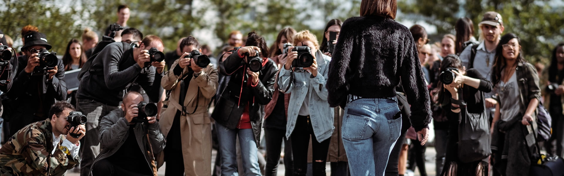 Paparazzi photographing model outside