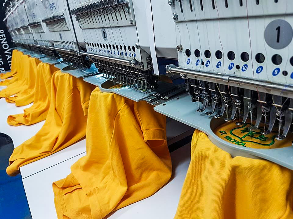 Embroidery machine printing a number of schoolwear polo shirts