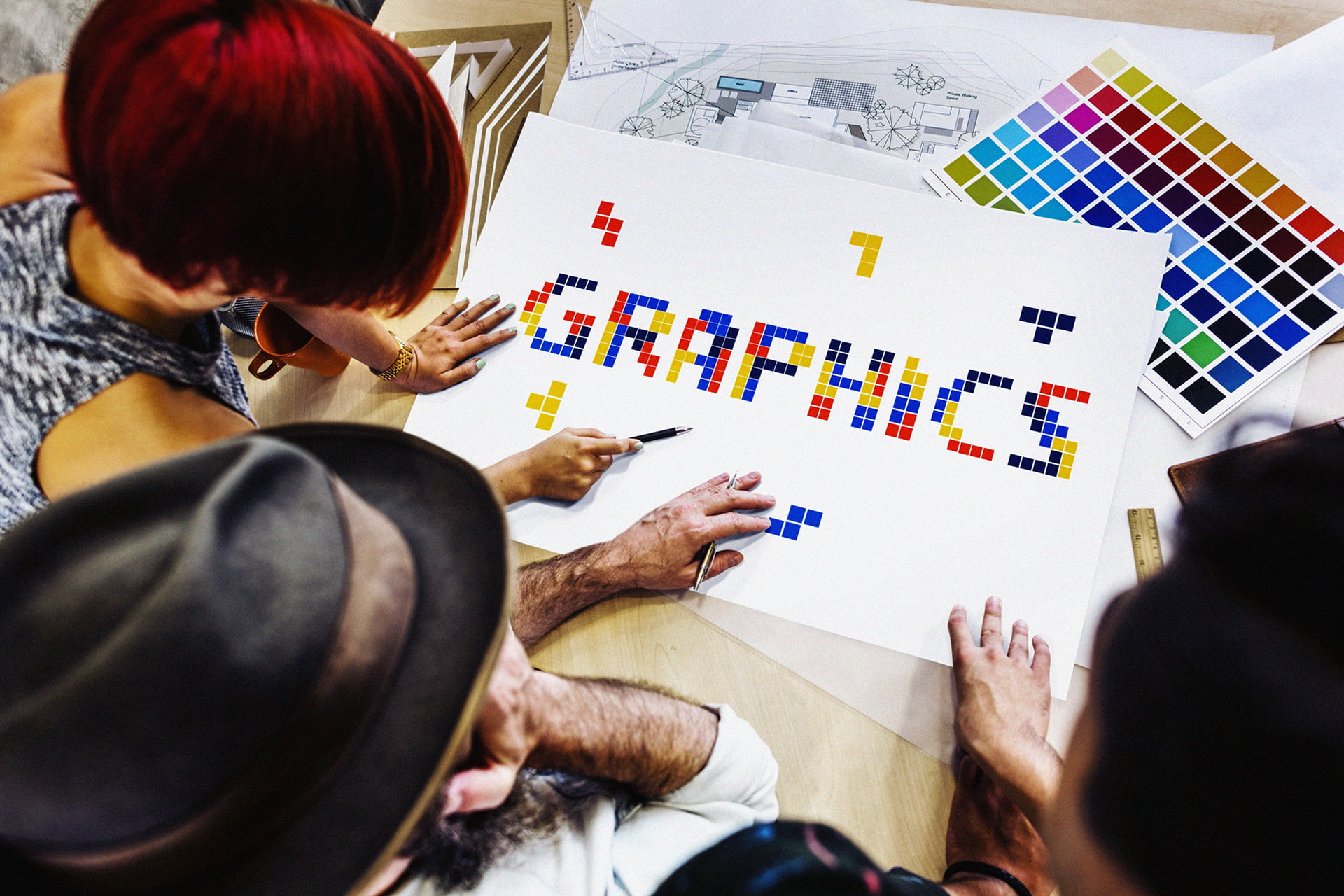 3 graphic designers discussing project at huge desk